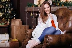 少妇坐长沙发,单独,在客厅的圣诞树前面 库存图片