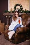 少妇坐长沙发,单独,在客厅的圣诞树前面 免版税库存照片