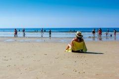 少妇坐面对海的长凳 免版税库存图片