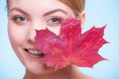 少妇女孩的面孔有红槭叶子的 免版税图库摄影
