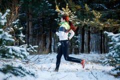 少妇女运动员的图片跑通过冬天森林的 免版税库存照片
