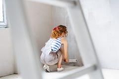 少妇她的新房绘画墙壁  库存图片