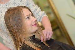 少妇安排头发剪由美发师在沙龙 免版税库存照片
