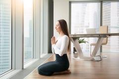 少妇实践的瑜伽在办公室 免版税库存照片