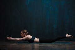 少妇实践的瑜伽对黑暗的墙壁 免版税图库摄影