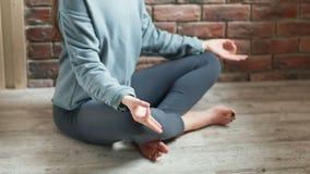 少妇实践的瑜伽户内 女性手特写镜头在莲花姿势的 股票视频