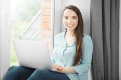 少妇工作在膝上型计算机并且坐在窗台 库存照片