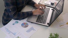 少妇工作在膝上型计算机的办公室的金融市场分析家,当坐在木桌上时 商人分析 影视素材