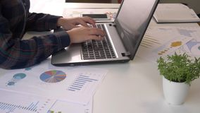 少妇工作在膝上型计算机的办公室的金融市场分析家,当坐在木桌上时 商人分析 股票录像