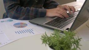 少妇工作在膝上型计算机的办公室的金融市场分析家,当坐在木桌上时 商人分析 股票视频