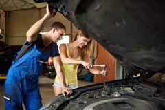 少妇帮助在车库的一辆汽车机械师修理汽车 免版税库存照片