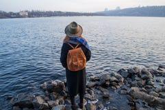 少妇帽子的和有站立在河岸的背包的,看日落或日出天际,后面看法 库存图片