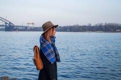 少妇帽子的和有站立在河岸的背包的,看日落或日出天际,后面看法 免版税库存照片