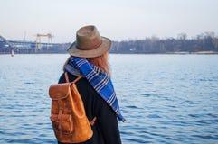 少妇帽子的和有站立在河岸的背包的,看日落或日出天际,后面看法 免版税库存图片