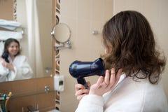 少妇干燥她的头发 免版税库存照片