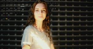 少妇庆祝与闪烁发光物混合的族种的特写镜头,她在金属篱芭前面跳舞 影视素材