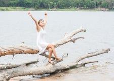 少妇开会舒展她的在树干的手在湖和 免版税库存照片