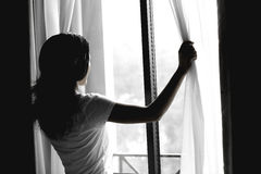 少妇开窗口 免版税库存照片