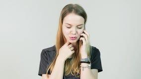 少妇微笑和谈话在她的在白色背景的手机 讲话一名年轻偶然的妇女的正面图  股票视频