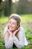 少妇微笑的说谎在草和花 免版税库存照片