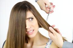 少妇惊吓了得到与剪刀的长的头发裁减被隔绝 免版税库存图片