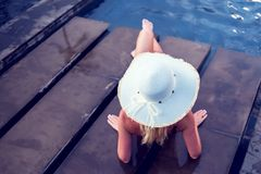 少妇愉快在大帽子放松在游泳池的, trav 库存图片