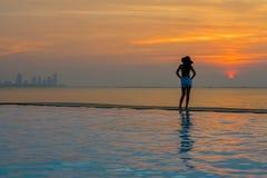 少妇愉快在放松在游泳池、在日落的旅行在海附近和海滩的大帽子 库存图片
