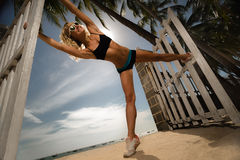 少妇扩大她的腿,当和做在海滩时的瑜伽 免版税库存图片