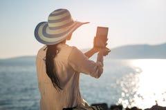 少妇拍与数字式片剂的一张selfie照片在海 免版税库存图片