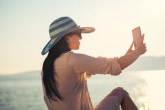 少妇拍与数字式片剂的一张selfie照片在海 库存图片