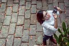 少妇拍从照相机的照片 免版税库存照片