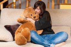 少妇拥抱玩具熊坐沙发 图库摄影