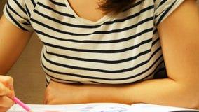 少妇拿着一支铅笔并且在家画 成人和孩子的着色 对应力消除 成人彩图 免版税库存图片