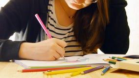 少妇拿着一支铅笔并且在家画 免版税库存图片
