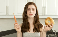 少妇拿着一棵红萝卜和一个百吉卷 免版税库存照片