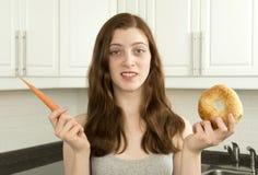 少妇拿着一棵红萝卜和一个百吉卷 免版税库存图片