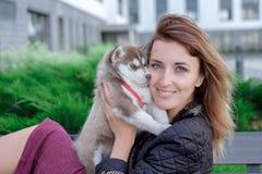 少妇拿着爱斯基摩她的最好的朋友小的宠物小狗在她的胳膊的 对狗的爱 免版税库存照片