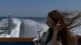 少妇按顺序在一艘移动的汽艇的投入她的头发在slo mo 影视素材