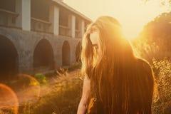 少妇掩藏她的与太阳选择聚焦被定调子的图象由后照的长的金发,太阳火光的面孔 免版税库存图片
