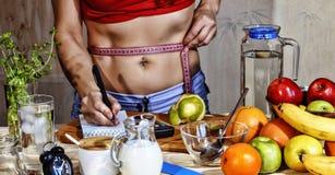 少妇措施 戒毒所 女孩测量腰部并且使用适当的营养 戒毒所饮料,成份,哑铃 Concep 库存图片
