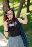 少妇摄影师,游人拿着一台照相机并且显示t 免版税图库摄影