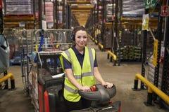 少妇操作拖曳拖拉机在配给物仓库里 免版税图库摄影