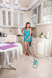少妇擦的地板在干净的厨房里 免版税库存图片