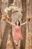 少妇放松的使用与叶子在秋天公园 库存照片