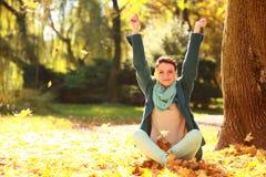 少妇放松的使用与叶子在秋天公园 免版税库存照片
