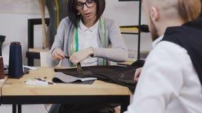 少妇时装设计师和她的顾客与坐在美丽的办公室的织品一起使用以不同 股票录像