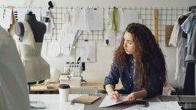 少妇时装设计师画夫人`服装剪影在书桌在现代车间 时装模特,缝合的项目, 股票视频