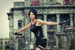 少妇是与一杆枪的侦探在一个被破坏的城市 免版税库存照片