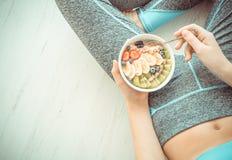 少妇是休息和吃一个健康燕麦粥在锻炼以后 库存照片