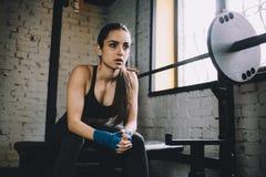 少妇有一些休息在坚硬锻炼以后在健身房 免版税图库摄影